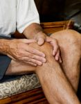 man massaging painful knee