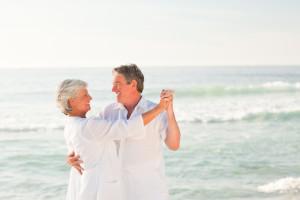 Happy Elderly Couple Dancing on the Beach